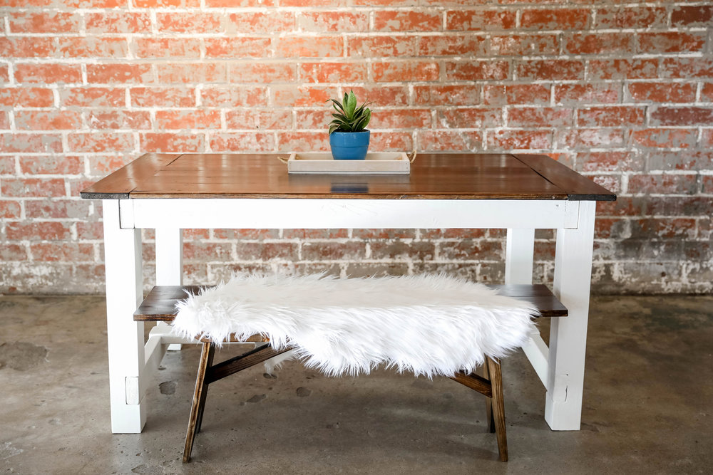 Farm style table and bench with a pop of color, accented by a faux fur rug piece