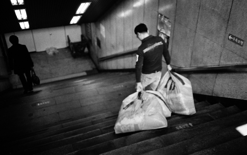 A photograph of a man carry bags in the subway, Seoul, South Korea