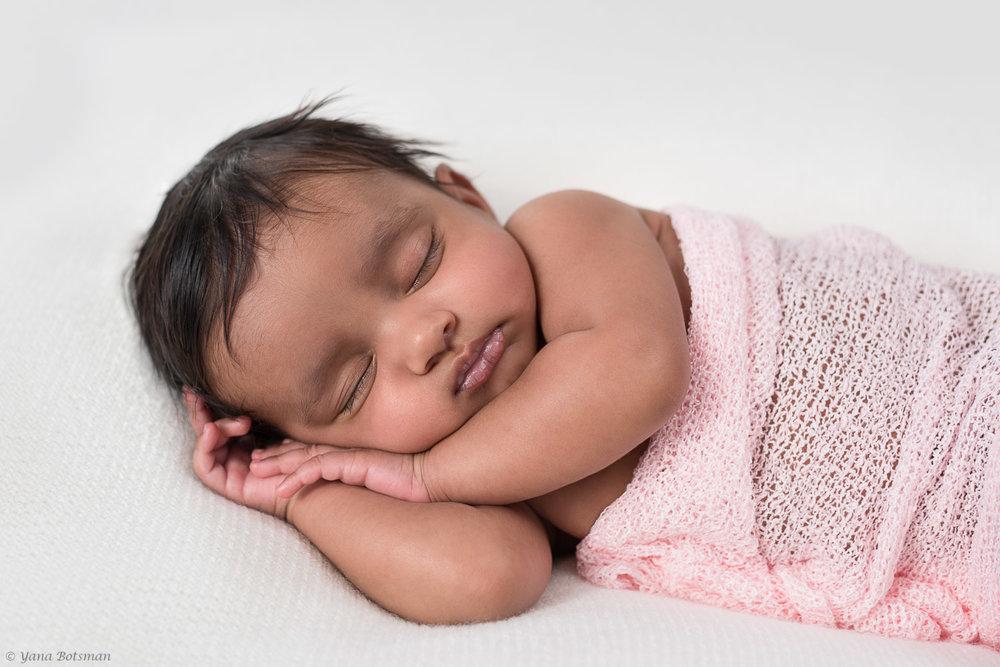 beautiful baby girl asleep on her side with hands under her cheek.jpg
