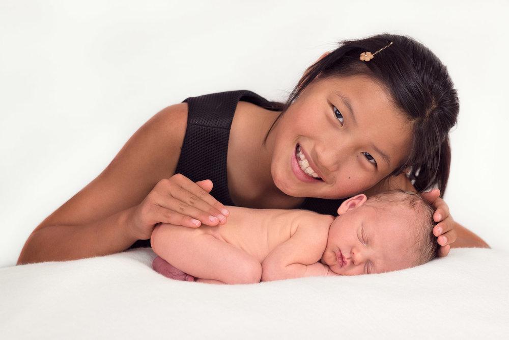sister loves her newborn brother.jpg
