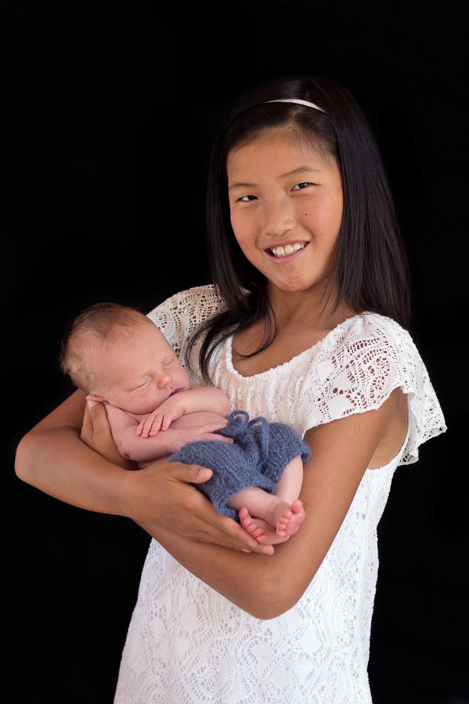 so happy holding her newborn brother.jpg