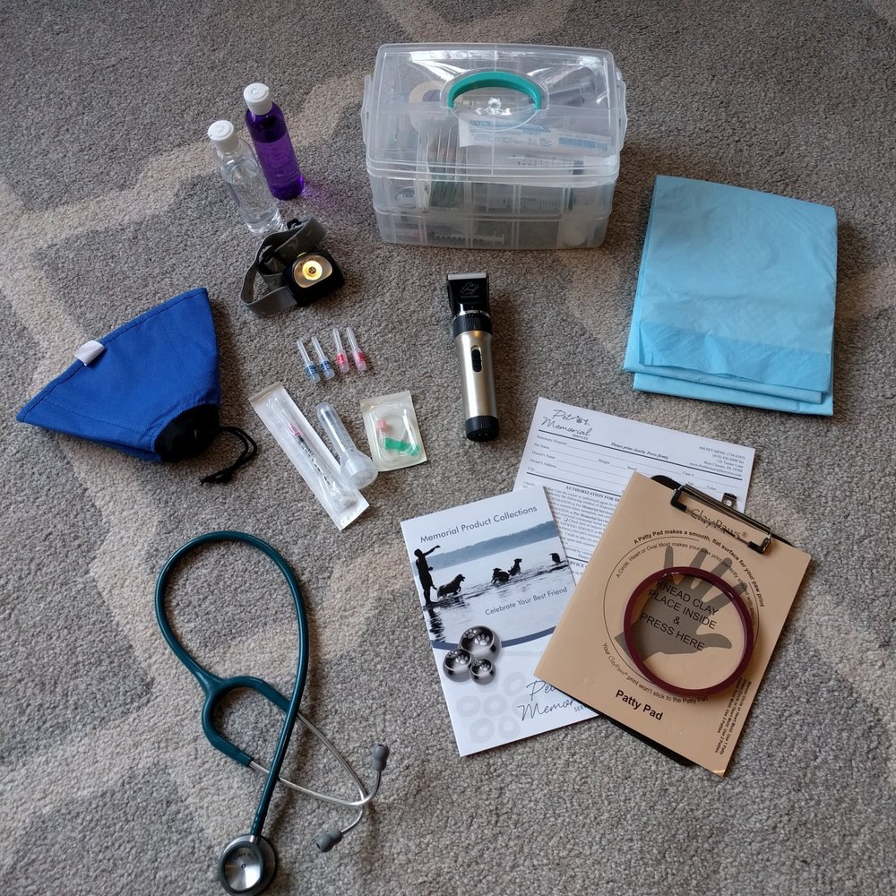 Some of the contents from my medical bag: At the top, I have alcohol and hydrogen peroxide, my tackle box of medical supplies, a headlamp in case the lights are too low for me to see you pet's veins, a soft e-collar for feisty cats or dogs (I also have a full set of muzzles in the car if needed. Thankfully I rarely need these), needles and syringes, clippers, pee pads, a stethoscope, information about specialty urns if desired, consent forms, and material to make a clay paw impression.