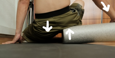 Here I use a foam roller , sitting on the edge brings the opposite end up , I push it down with the hand to increase the point of contact where the arrow on the roller is .