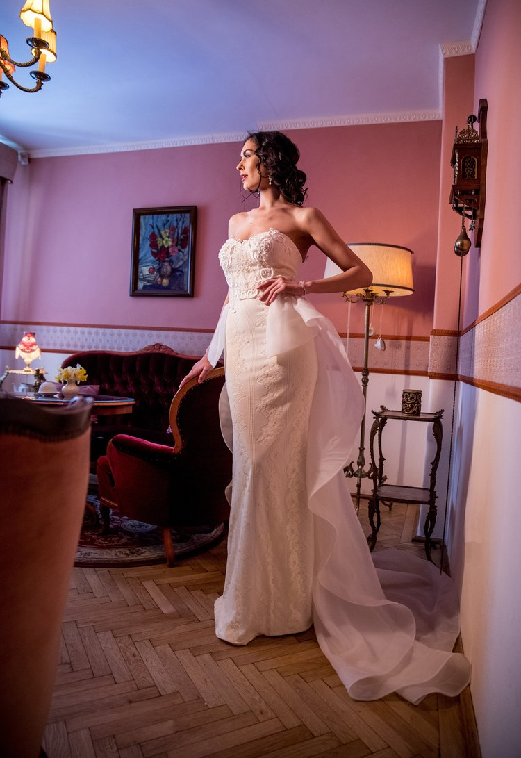 Featured :  Arum  is a stunning sleeveless wedding dress crafted in dark ivory lace, adorned with an organza skirt with a back peplum cut at the waist. Walking down the aisle in the dress is going to be a memorable event.