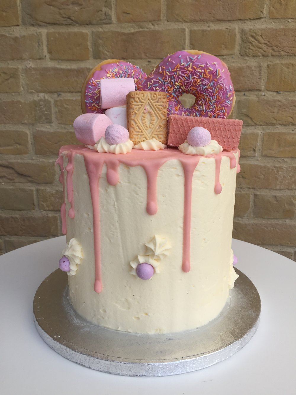 A fun birthday drip cake decorated with donuts, chocolate shards and Oreos. Drip cakes made to order in Kings Lynn and Norfolk