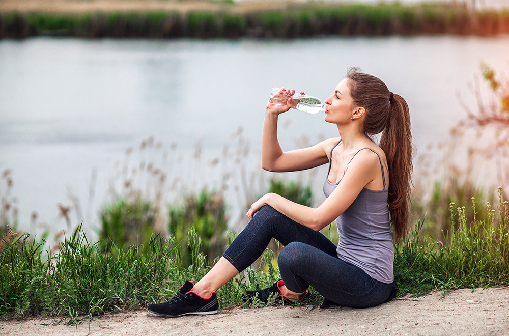 Woman drinking bottled water by river in Brookline, MA