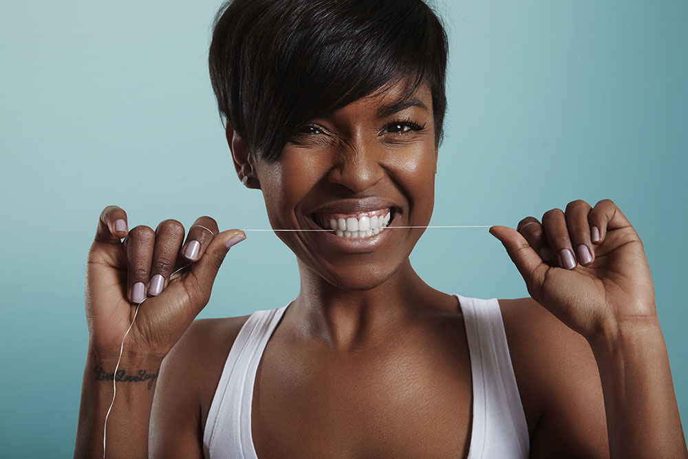 Woman flossing for good hygiene to prevent sensitivity