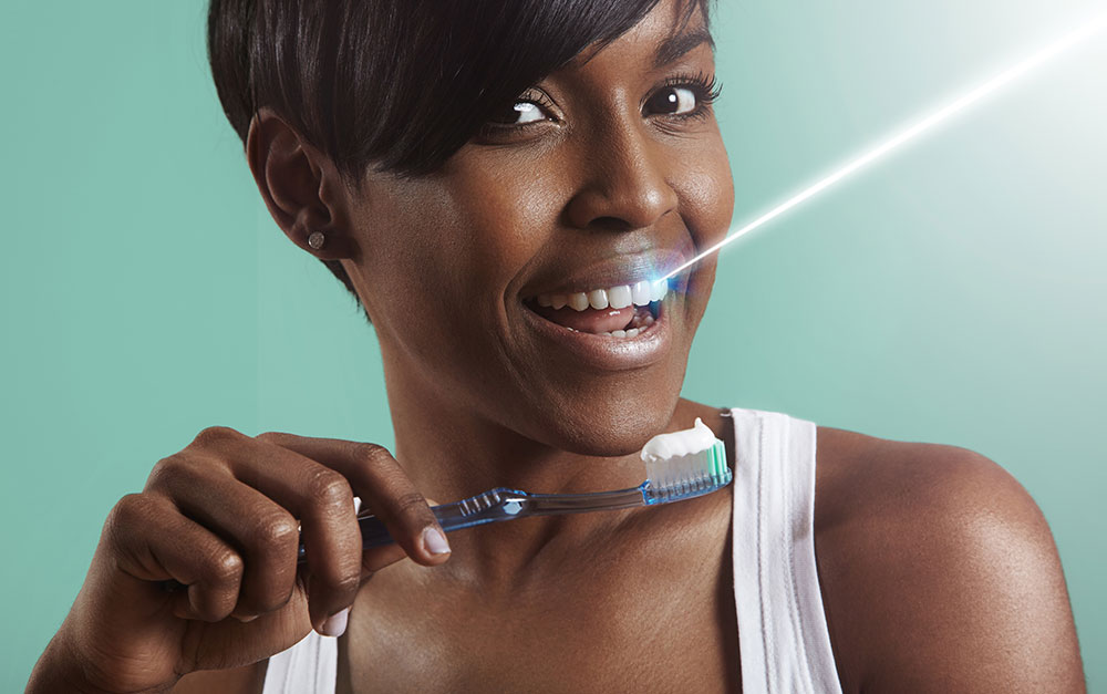 Woman with shining teeth using soft toothbrush