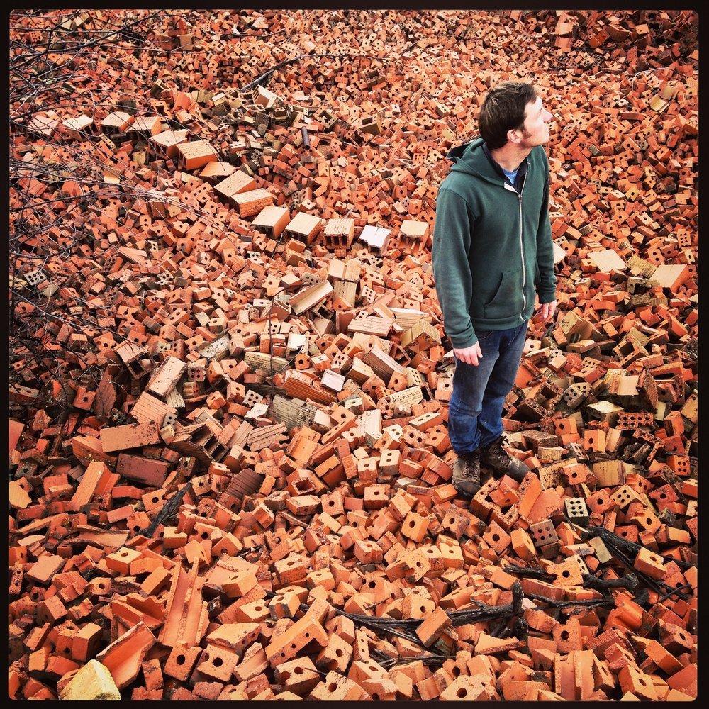 Josh Copus_portrait with brick pile_large.jpg