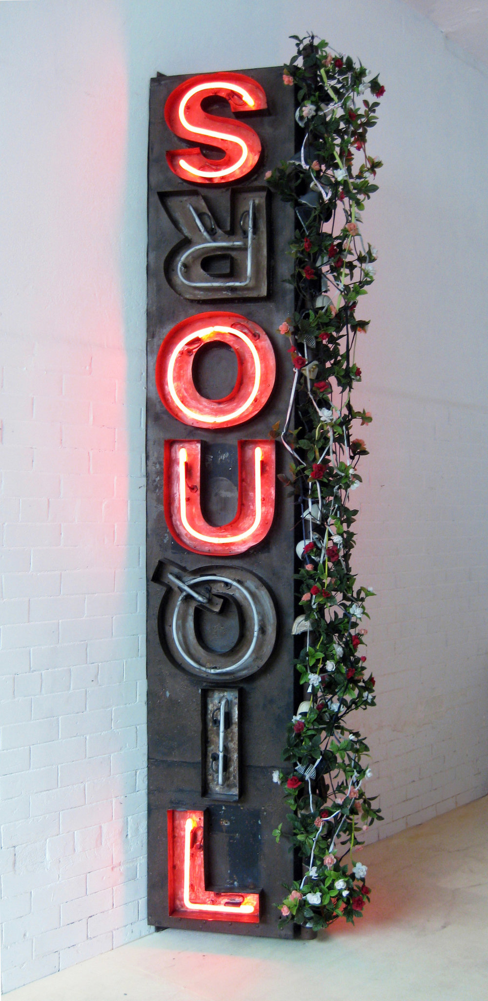 West Liquorsoul  2009, Metal and neon sign, wood with artificial flowers, pvc tubing, shoelaces and shoe tips  124 x 34 x 28 inches