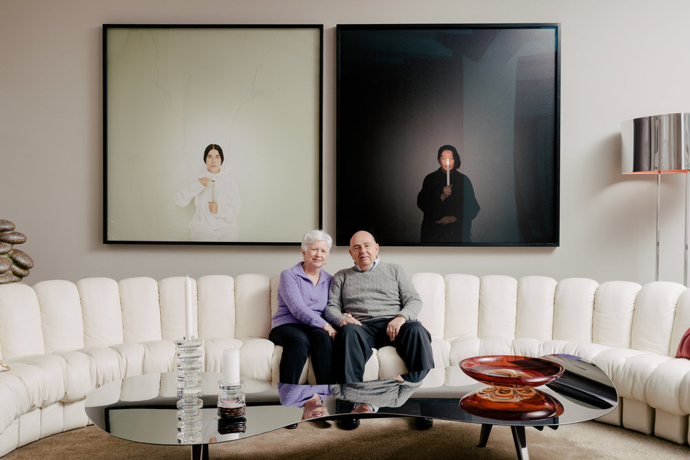 "Ron and Ann Pizzuti with Marina Abramovic's ""Artist Portrait With a Candle (C),"" left, and ""Artist Portrait with a Candle (B)."" At bottom left is Sofie Lachaert's ""Shunga Candleholder"" atop Ron Arad's ""Paved With Good Intentions Table 44.""CreditMarina Abramovic and Sean Kelly Gallery/Artists Rights Society (ARS), New York; Sofie Lachaert, via Artists Rights Society (ARS), New York; Daniel Dorsa for The New York Times"
