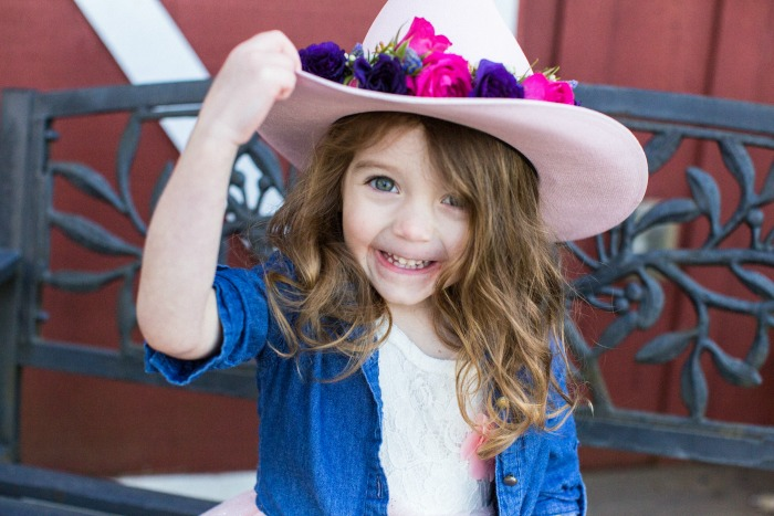 My Addy, proudly showing off her floral crown-adorned cowgirl hat.
