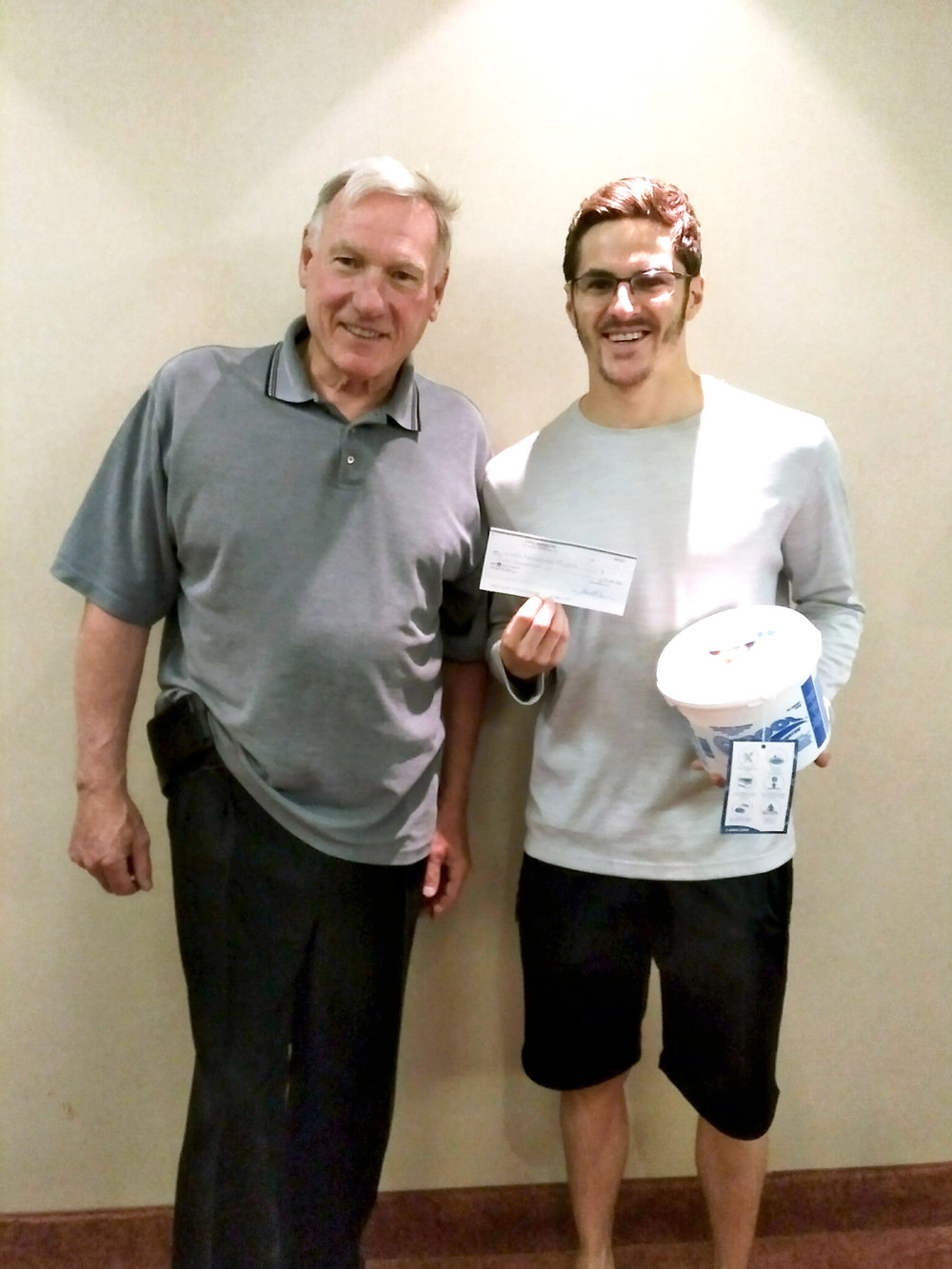 Gordie Michie receives his first sponsorship cheque from Pres. Jim Harris at C Pool corporate headquarters.