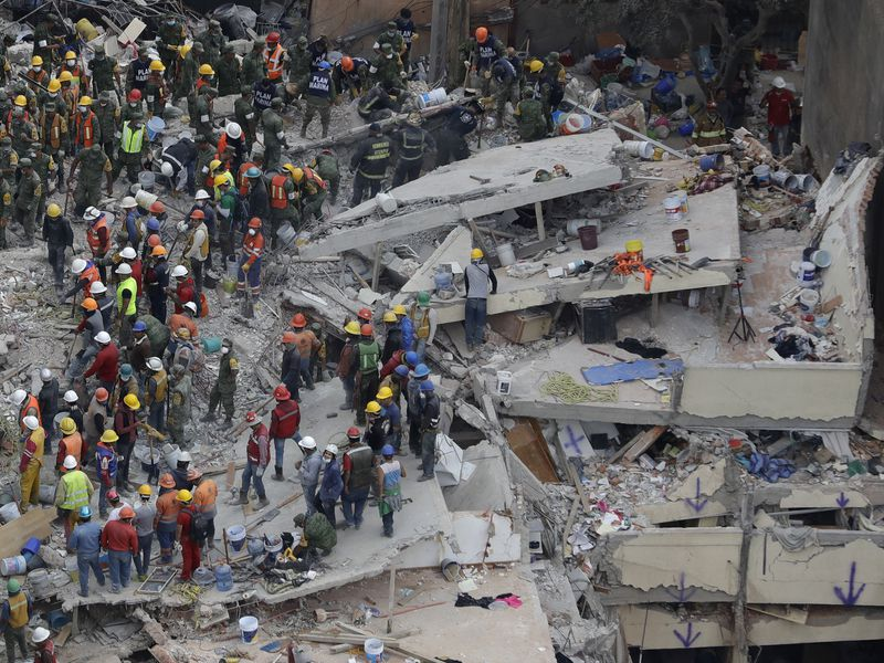 Rescue workers search for survivors among the rubble of a collapsed building in Mexico City. Structures throughout the capital were devastated during yesterday's earthquake. (Associated Press)