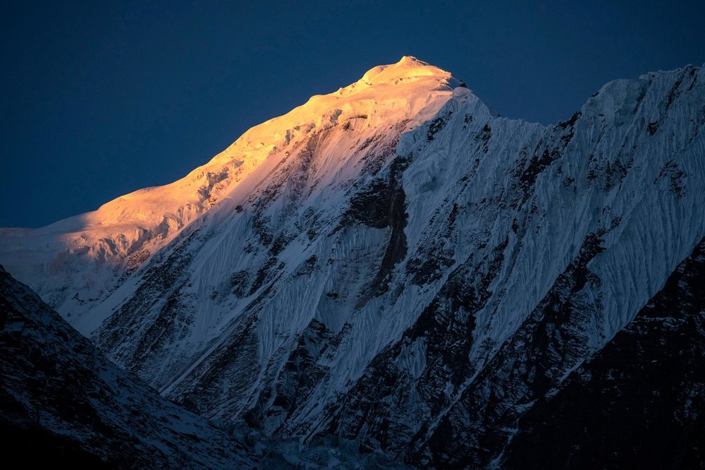 Sunrise strikes the Himalayan peaks on November 8, 2018, as seen from Manang, Nepal. PHOTOGRAPH BY DONALD MIRALLE/ GETTY LUMIX