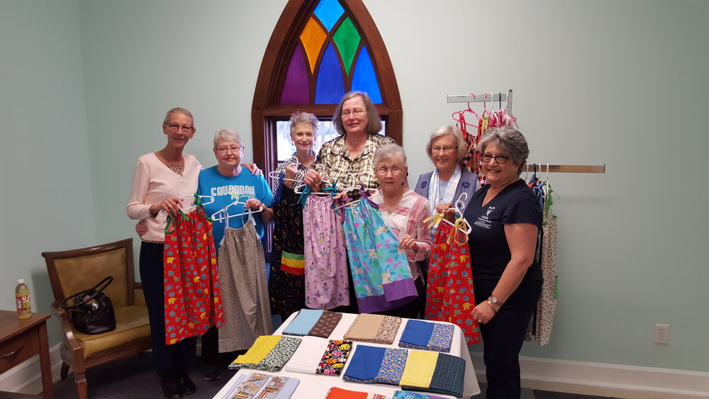 Ladies from the church showing dresses they sowed to support CASA.