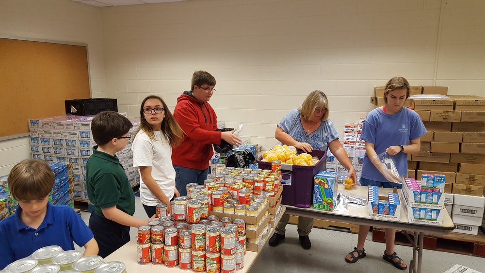 Youth packing food for Backpack Buddies of Effingham