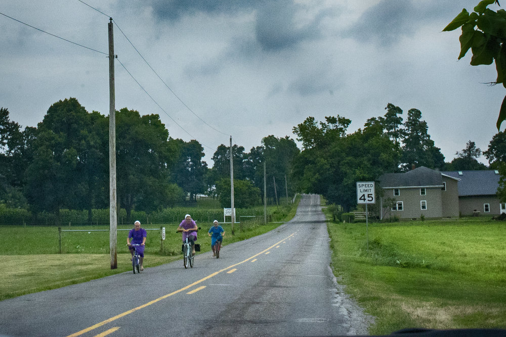 Amish girls on bicycles here in my home region of Northern Indiana. The Amish don't wish to be photographed, but the prohibition is becoming less strict as there are cameras everywhere these days. My general rule is that if individuals can't be identified, the Amish don't mind as much (some don't mind at all, but that's still rare). Some will allow photographs as long as they aren't asked to pose, since posing would be a demonstration of pride, which is discouraged in the Amish religion.