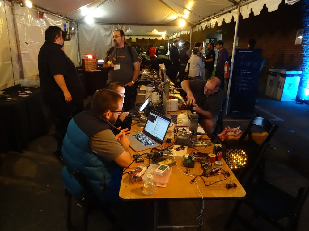 Cube at lower right cheering the badge hacking table on late into the night (Photo by Boian Mitov:  http://labpacks.blogspot.com/2017/11/pictures-from-hackaday-la.html )