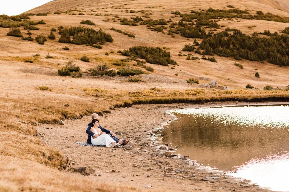 sitting along the alpine lake shoreline | Rocky Mountain post-wedding adventure session | Best Colorado wedding photographers