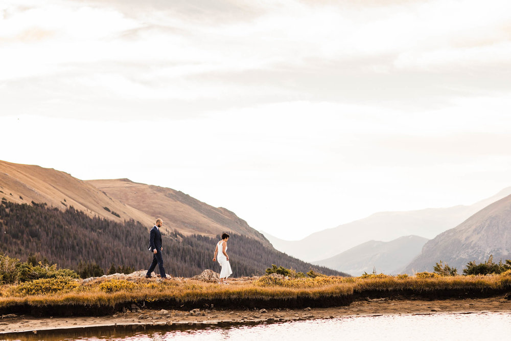 couple walking by an alpine lake | Rocky Mountain post-wedding adventure session | wedding photographers in Colorado