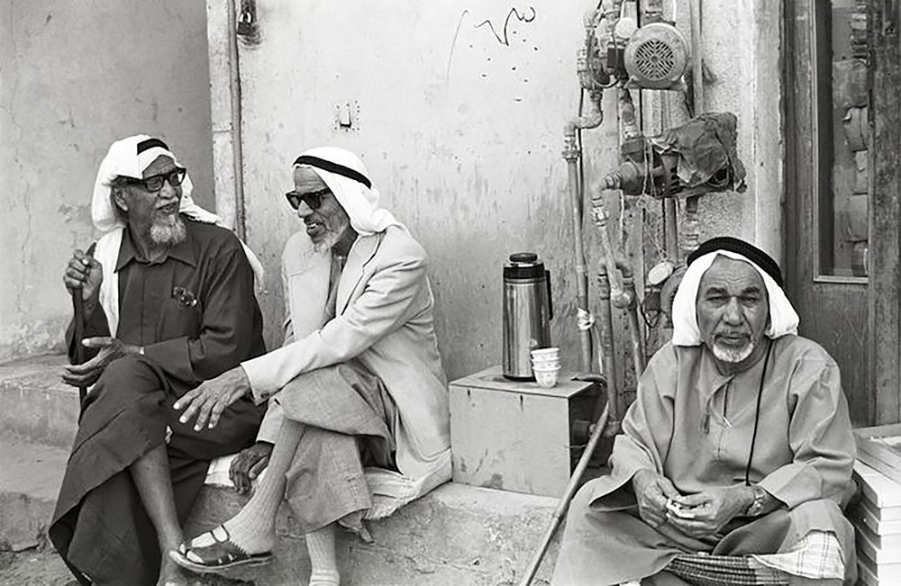Dated 1975, curated by Anita Van Der Krol. Elderly men in the old gold souk in Dubai, in particular middle man showcasing a sense of fashion different from other men in said time wearing peshwari sandals and sunglasses.