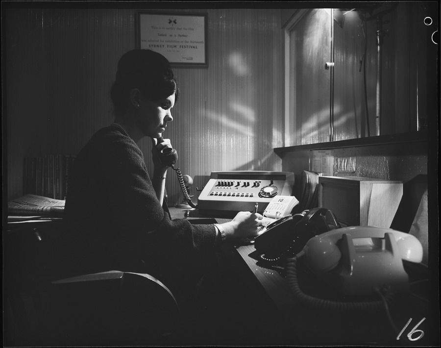 Female at desk with two telephones. Date on calendar: 10th October, 1967. Archives New Zealand