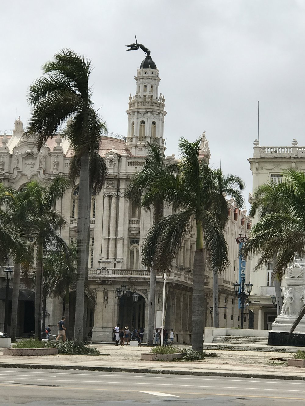 One of the four statues atop the Gran Teatro de Havana knocked horizontal from the storm. The others were all still vertical. Later the day, a crew was out taking down the bent over statue. There was an enormous crowd of people out watching and taking pictures of the process.