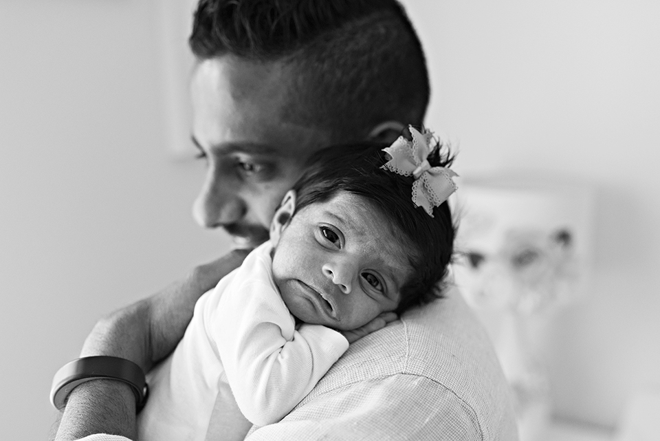 dad holding newborn with lots of hair and a bow southington connecticut newborn photographer