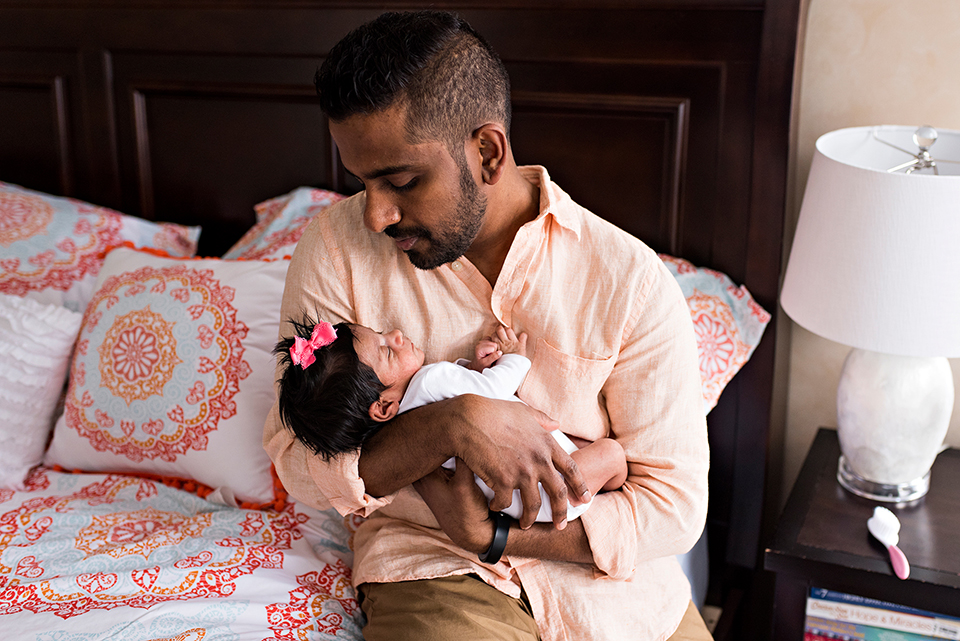 dad holding newborn daughter in bed southington connecticut newborn photographer