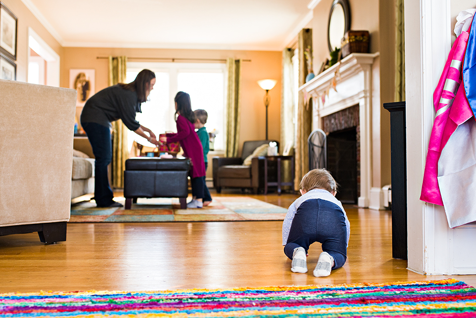 baby crawling into living room while mom plays with kids west hartford ct documentary family photography