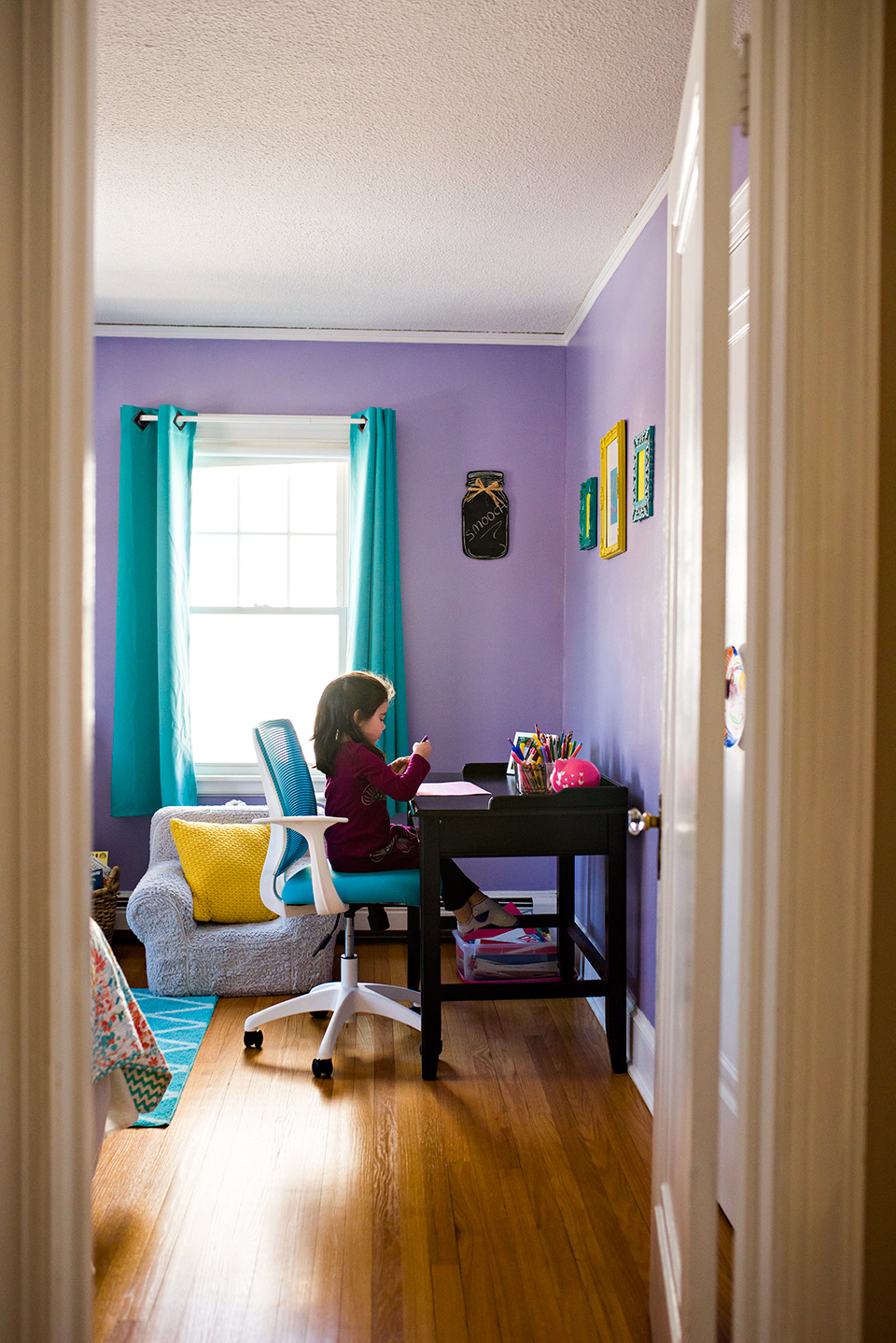 looking in on girl from doorway coloring on her desk in bedroom west hartford ct family photography documentary