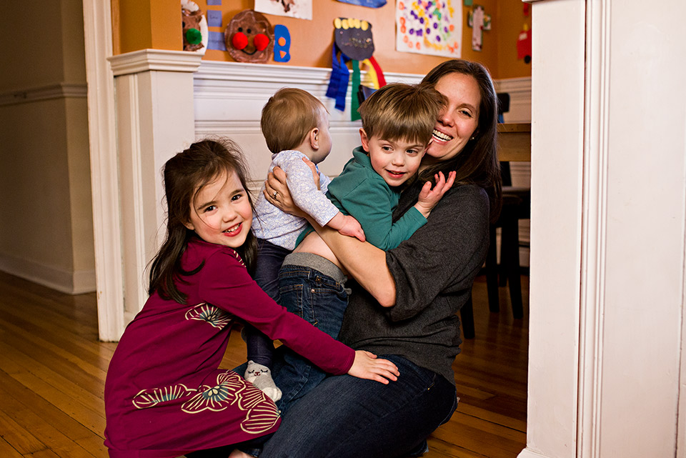 children climbing on and hugging mom in kitchen west hartford ct family documentary photography