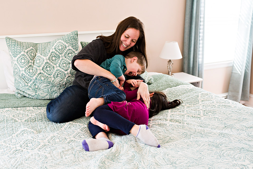 mom tickling son and daughter on master bed west hartford ct family documentary photography