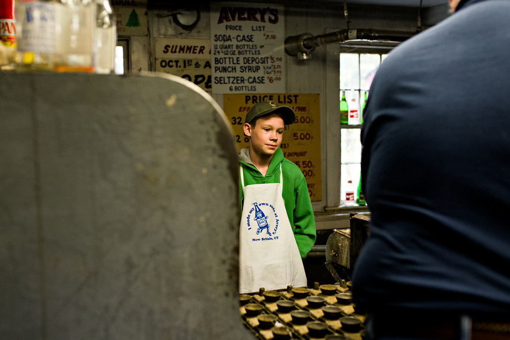 boy watching soda bottles get washed at averys soda new britain connecticut lifestyle photography