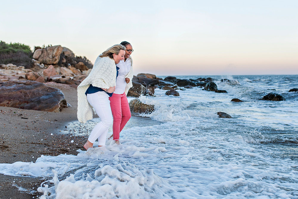 two women running into water at hammonasset beach connecticut engagement photography