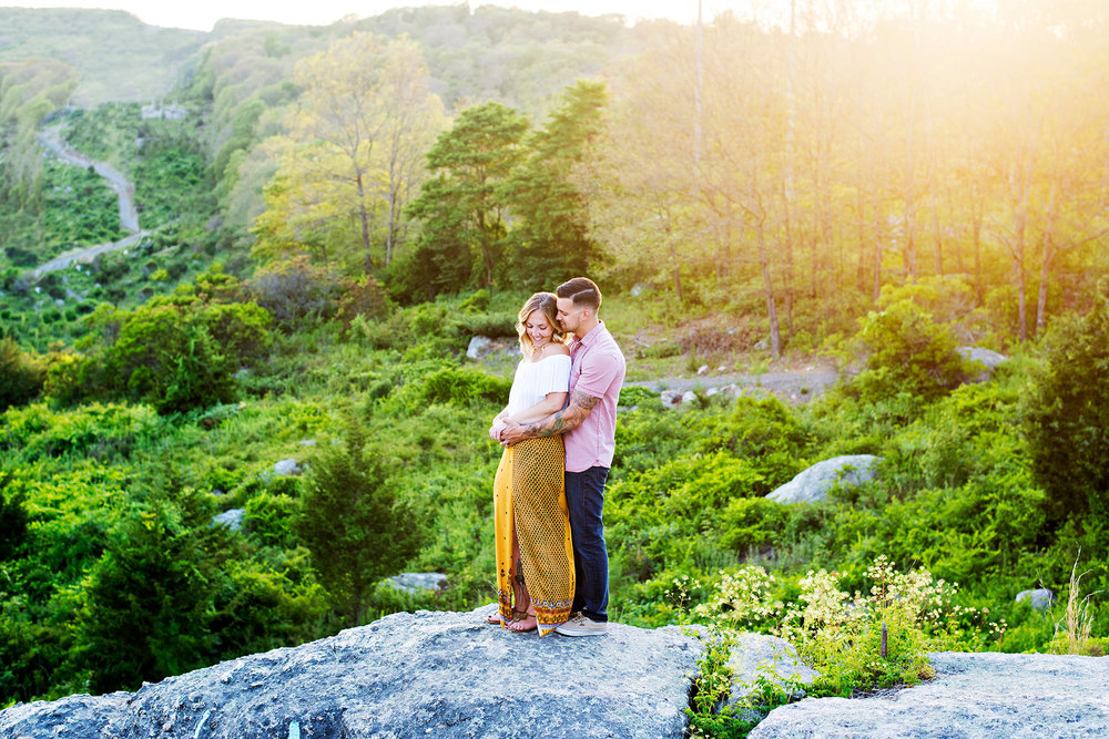 couple standing on rocky cliff at sunset Middletown, Connecticut engagement photography