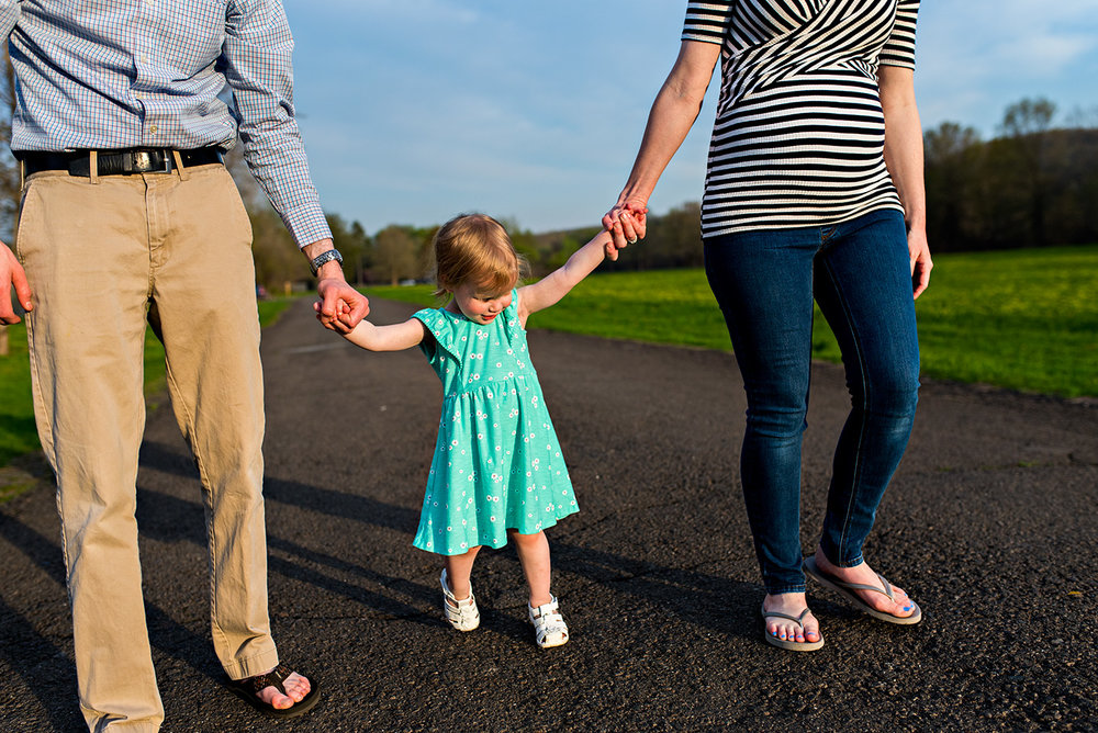 daughter holding mom and dads hand walking in field at haddam meadows in haddam connecticut lifestyle maternity photography