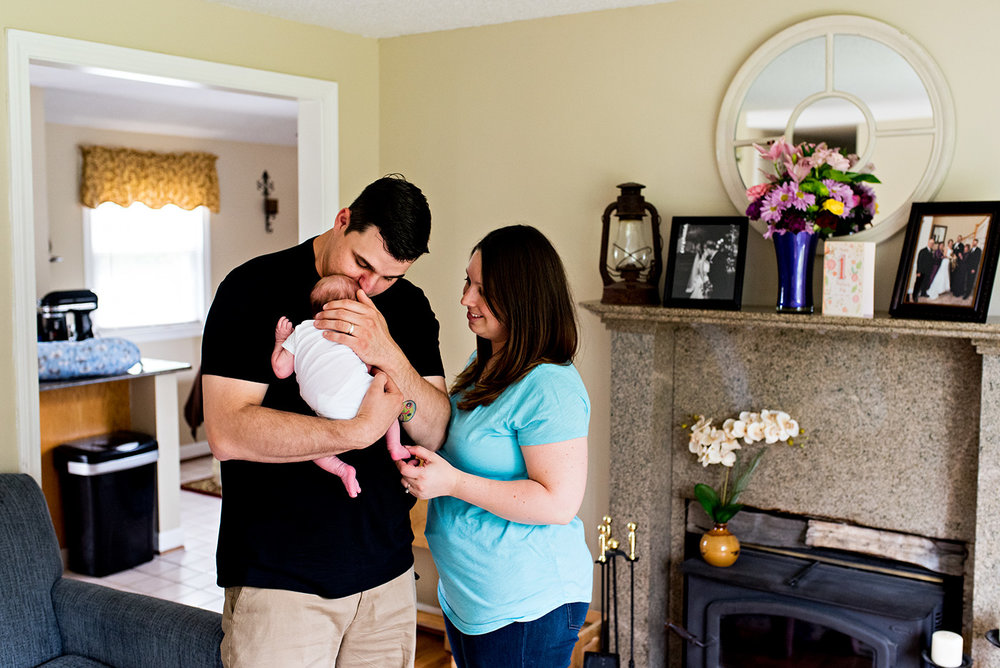dad kissing newborn in living room southington ct newborn photography