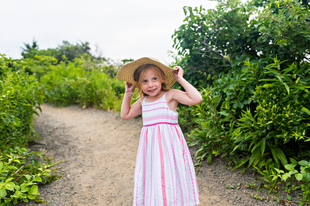 little girl holding hat at clinton, ct beach family photography