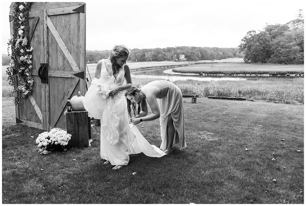 sister helping bride with wedding dress at connecticut backyard wedding
