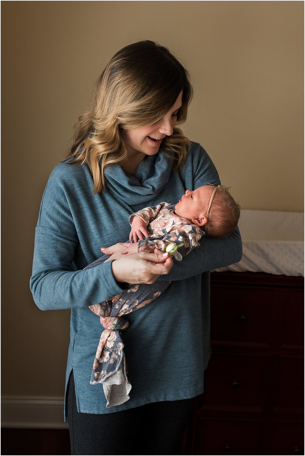 Mom holding newborn daughter during CT baby photography session.