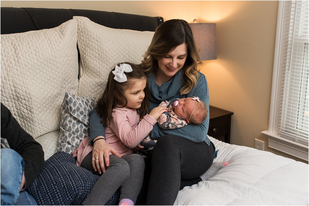 Big sister helping to hold newborn baby with Mom during CT newborn photography session.