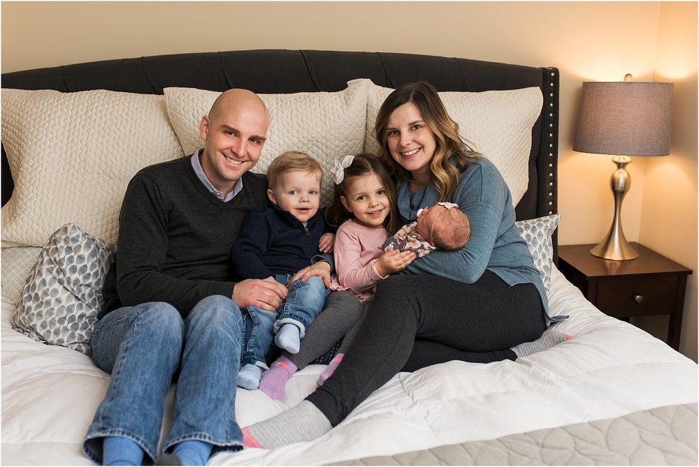 Mom and dad snuggling with children during an at home baby photography session in New Haven, CT