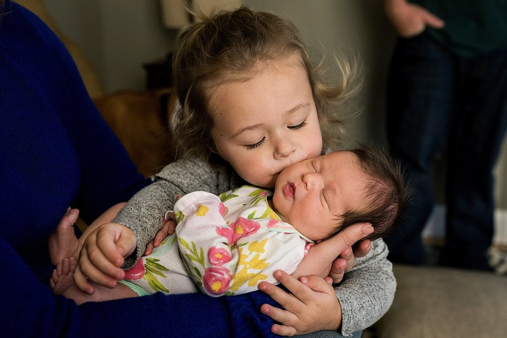 toddler kissing her new baby sister during their Newborn Photography in Southington, CT