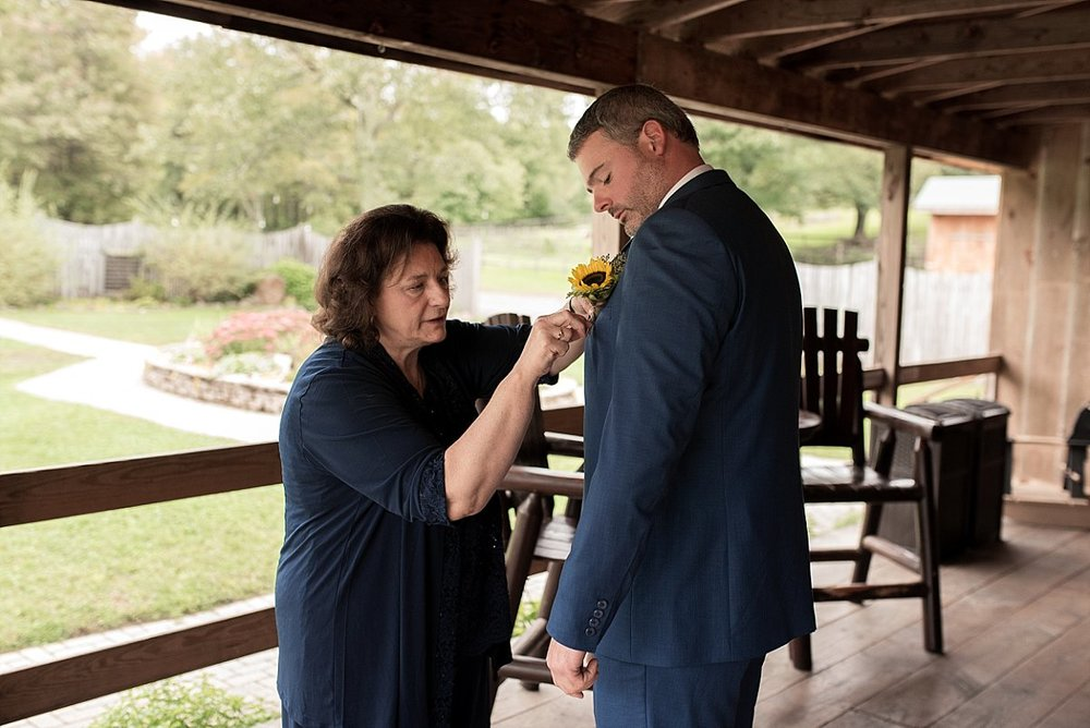 Mother of the groom pinning his flower onto his suit jacket at wood acres farm in terryville connecticut wedding