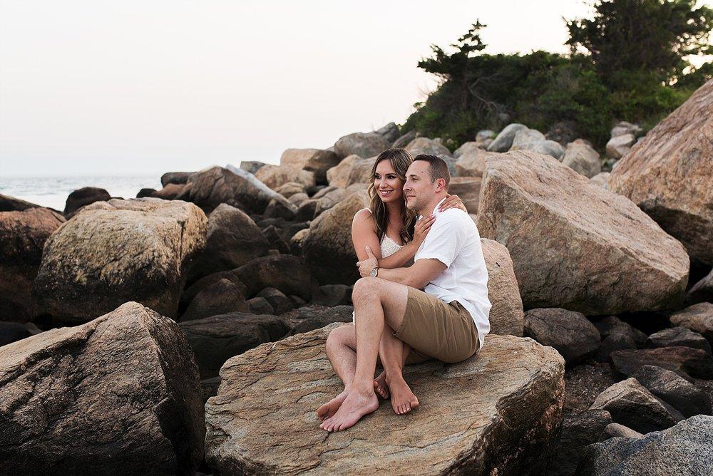 engaged couple sitting on rocks in madison, ct