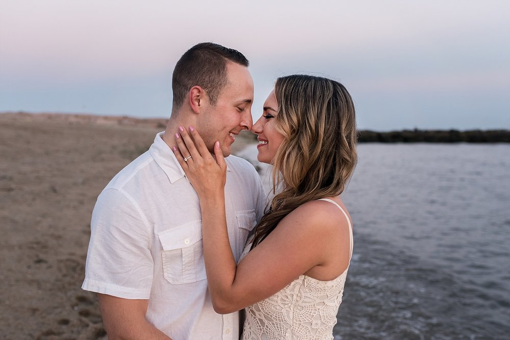 engaged couple kissing at sunset on the beach in connecticut