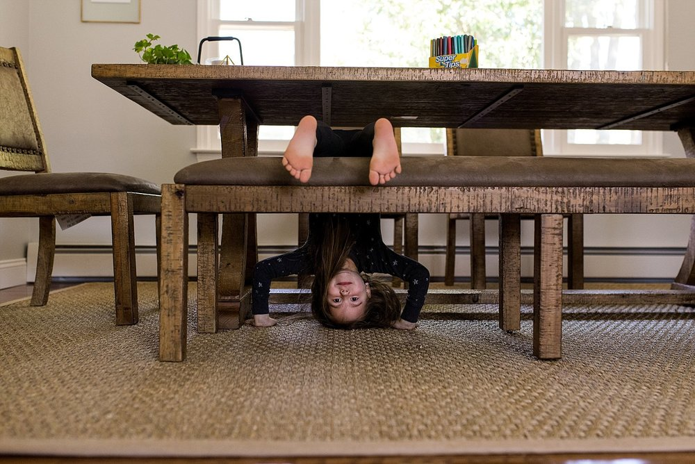 girl hanging upside down on dinning room table at her South Windsor CT family photo session