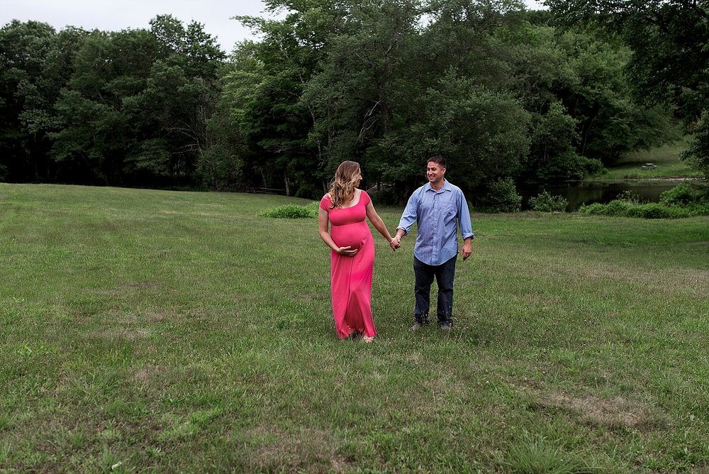 husband and wife holding hands in a field during New Haven County CT photography session